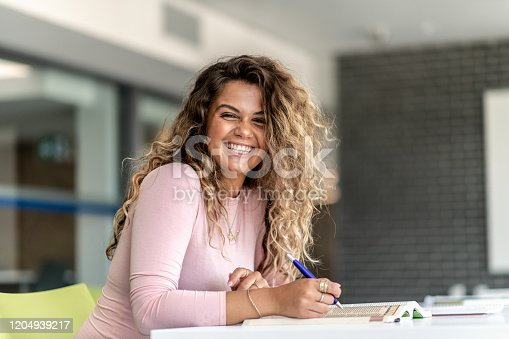 An attractive female of Italian descent sits in a room on campus doing homework. She is dressed casually and wearing a light pink shirt as she looks up from her books to smile.