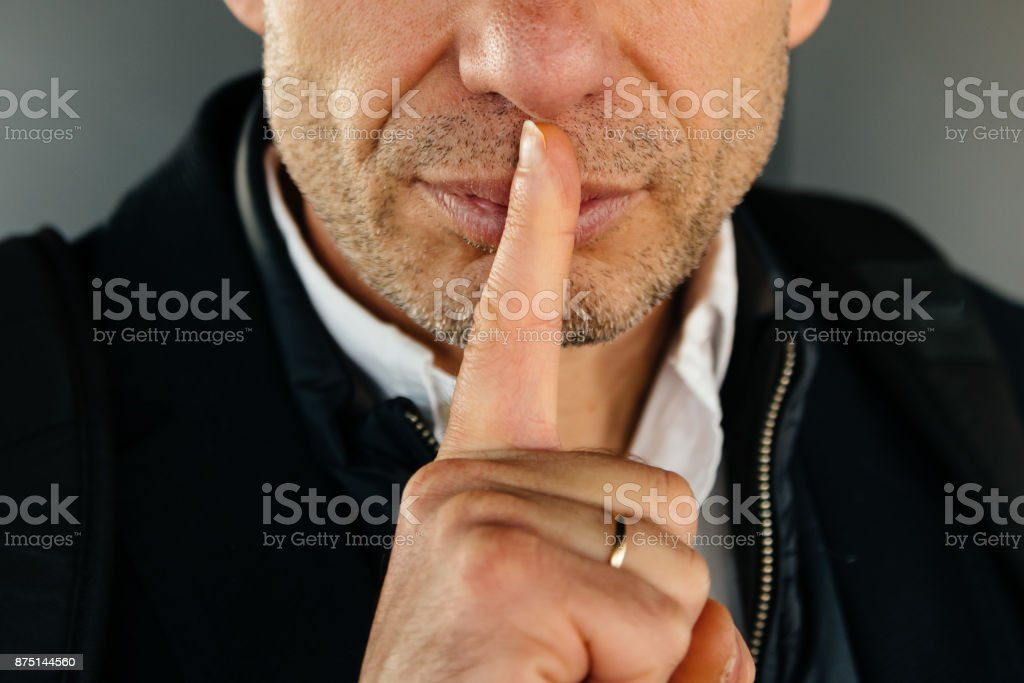 Attractive unshaved adult man with finger on lips making silence stock photo