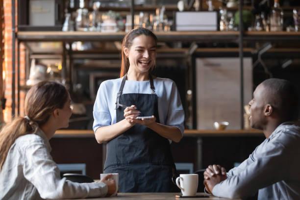 camarera atractiva riendo de broma de hombre afroamericano, sirviendo a los clientes - restaurante fotografías e imágenes de stock