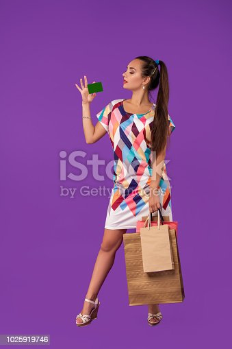 Attractive woman 20s in dress holding shopping packages and showing green credit card isolated over purple background. Studio shot. Copy space