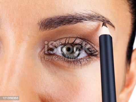 istock Attractive woman applying eyebrow pencil 121356353
