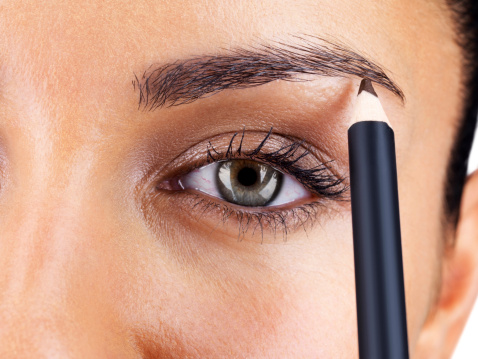 Attractive woman applying eyebrow pencil stock photo