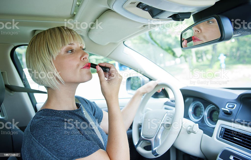 Atraente mulher aplicando compõem em seu carro - foto de acervo