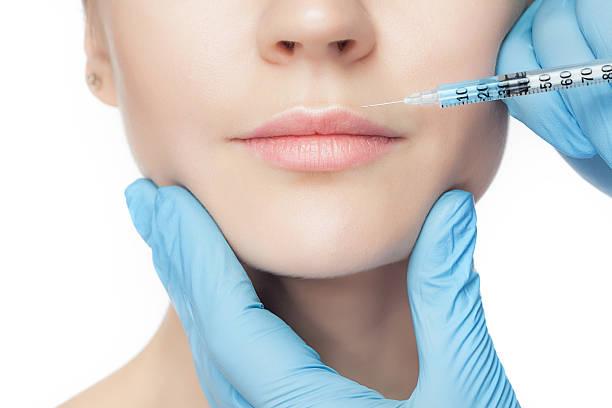 attraktive frau am plastische chirurgie mit spritze in ihr gesicht - nadeldesigns stock-fotos und bilder