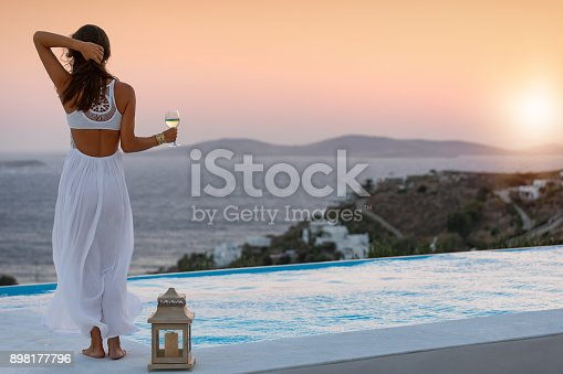 istock Attractive woman at the pool enjoys the sunset over the mediterranean sea 898177796