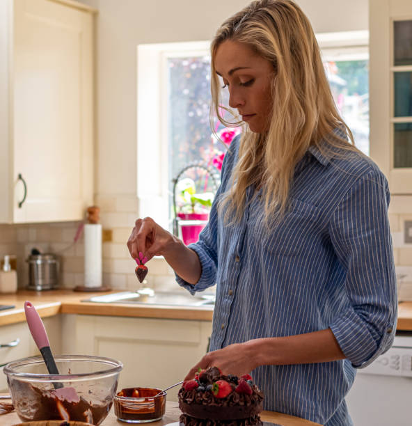 Attractive woman baking a cake at home, dipping a strawberry in chocolate stock photo