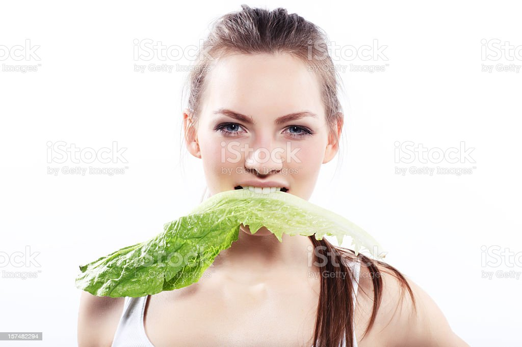 Attractive woman biting lettuce royalty-free stock photo