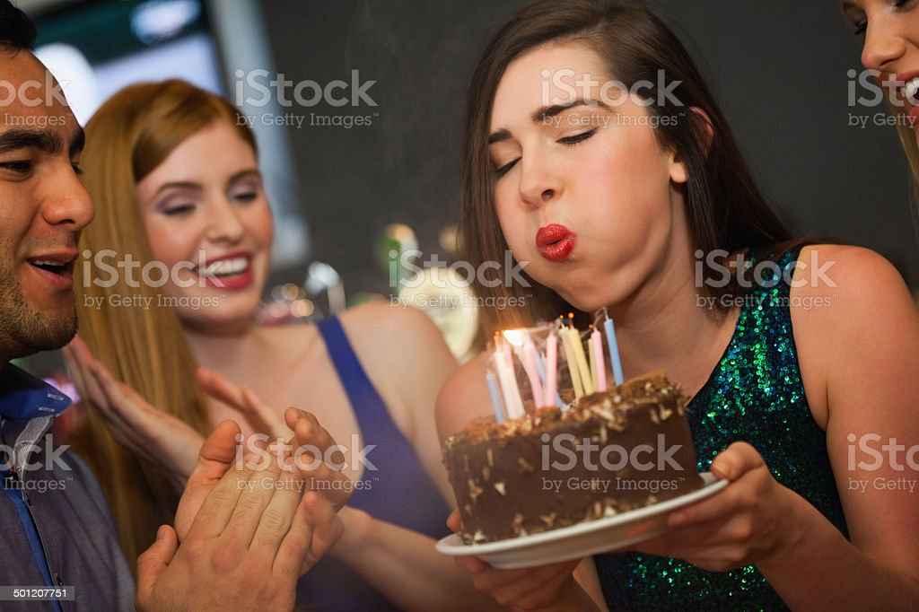 Attractive woman blowing the candles on her birthday cake stock photo