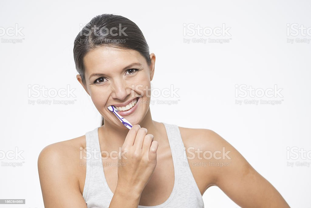 Attractive woman brushing her teeth stock photo