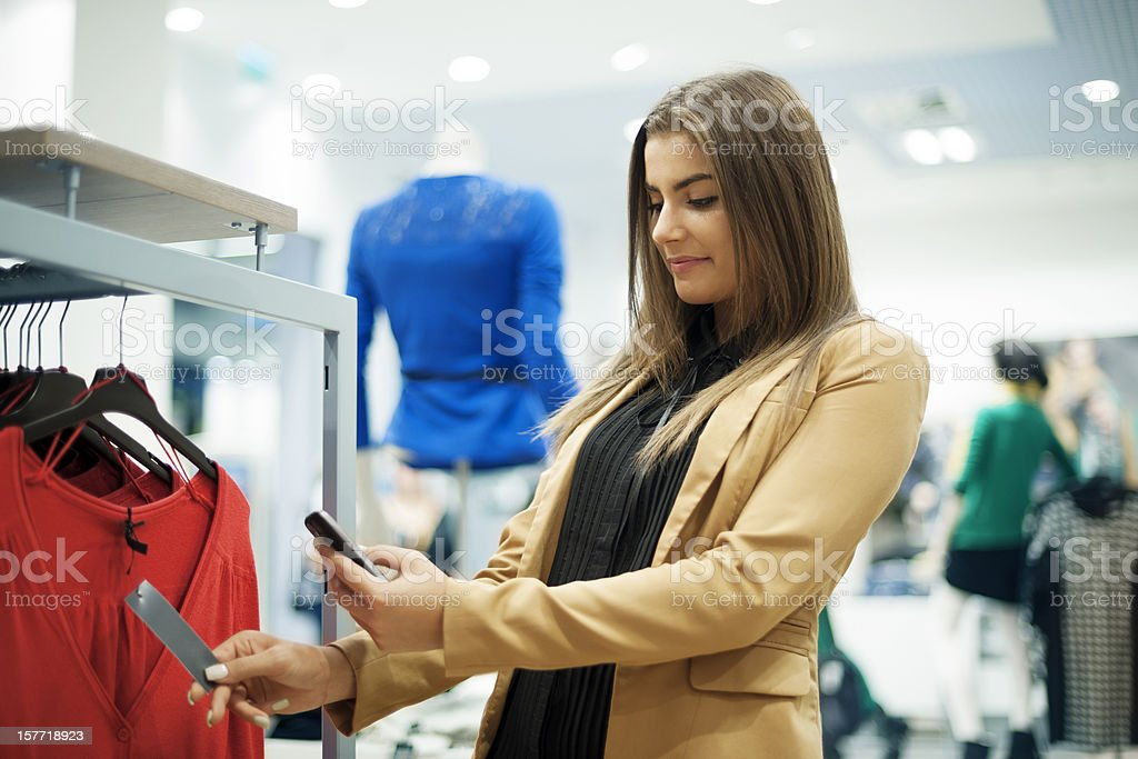 Attractive woman checking bar code in shopping mall stock photo