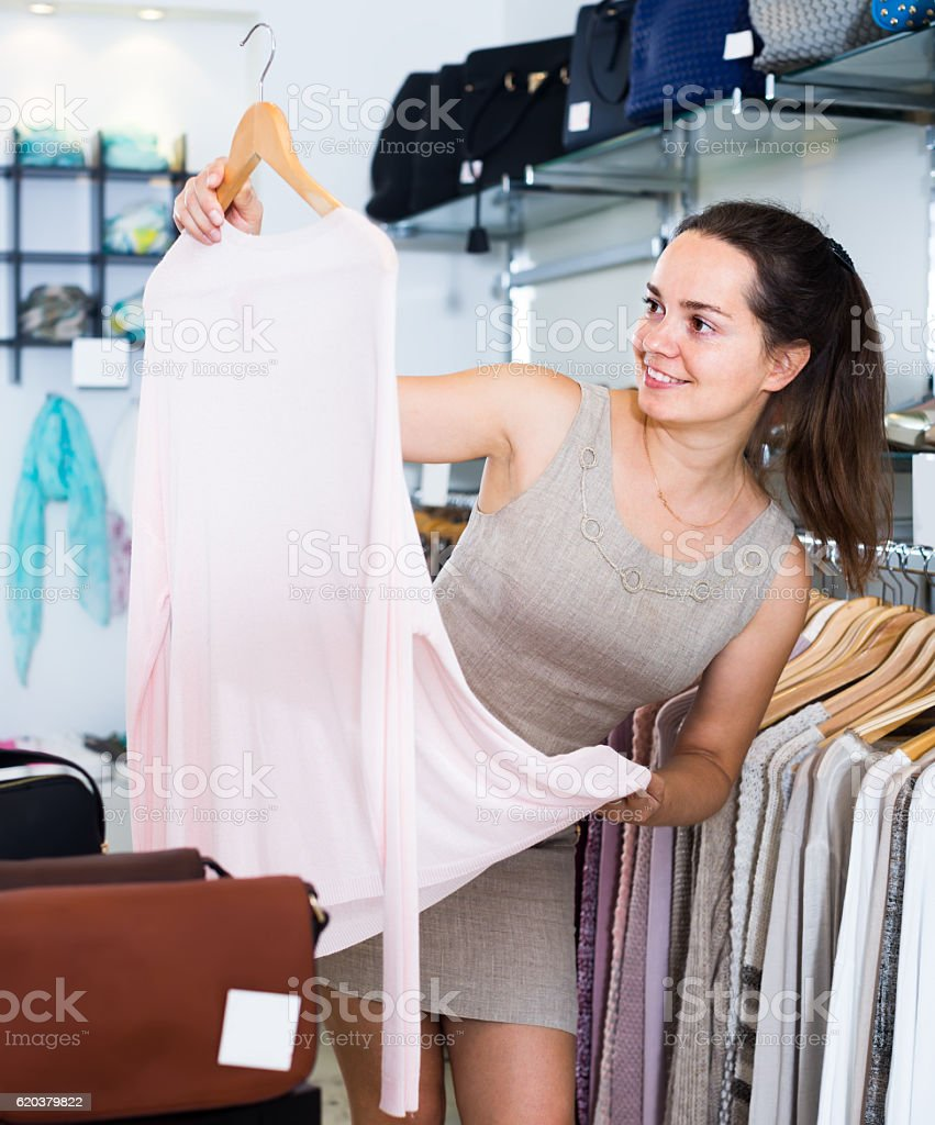 attractive woman choosing new blouse in apparel shop zbiór zdjęć royalty-free