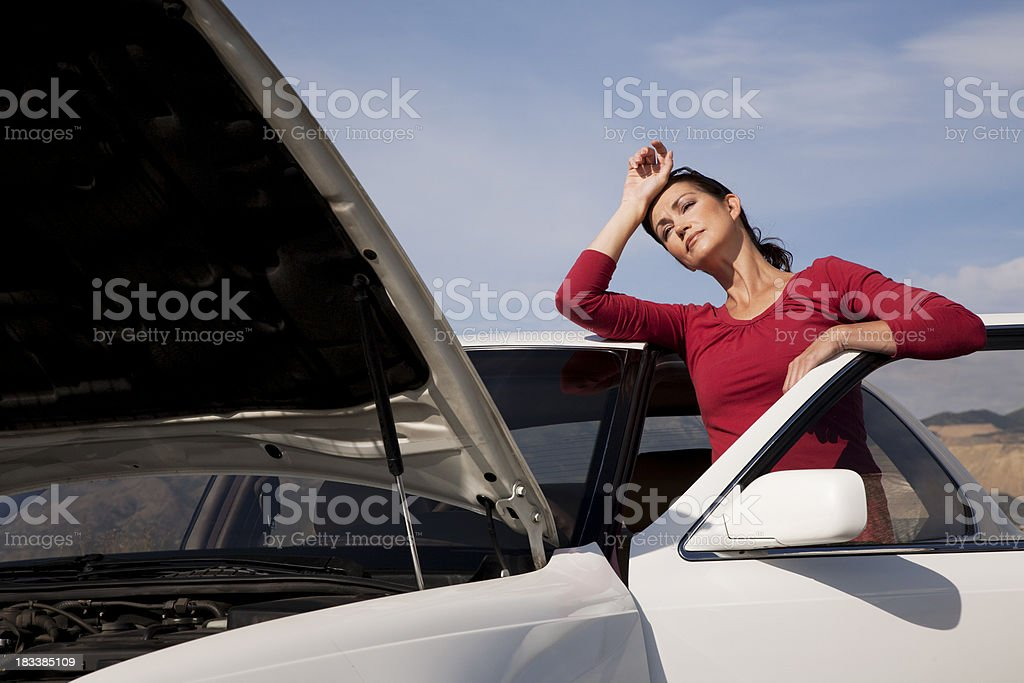 Attractive woman clearly fed up with her broken down car royalty-free stock photo