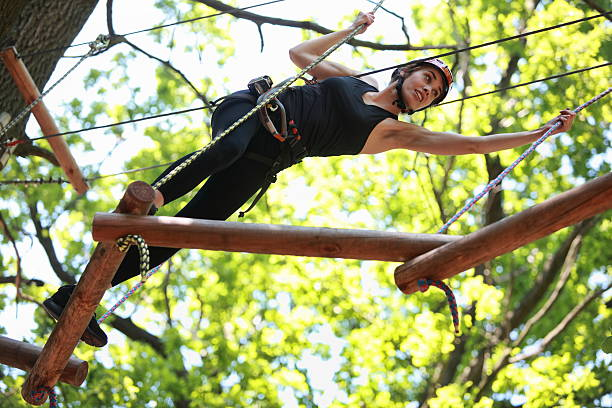 attractive woman climbing in adventure rope park stock photo