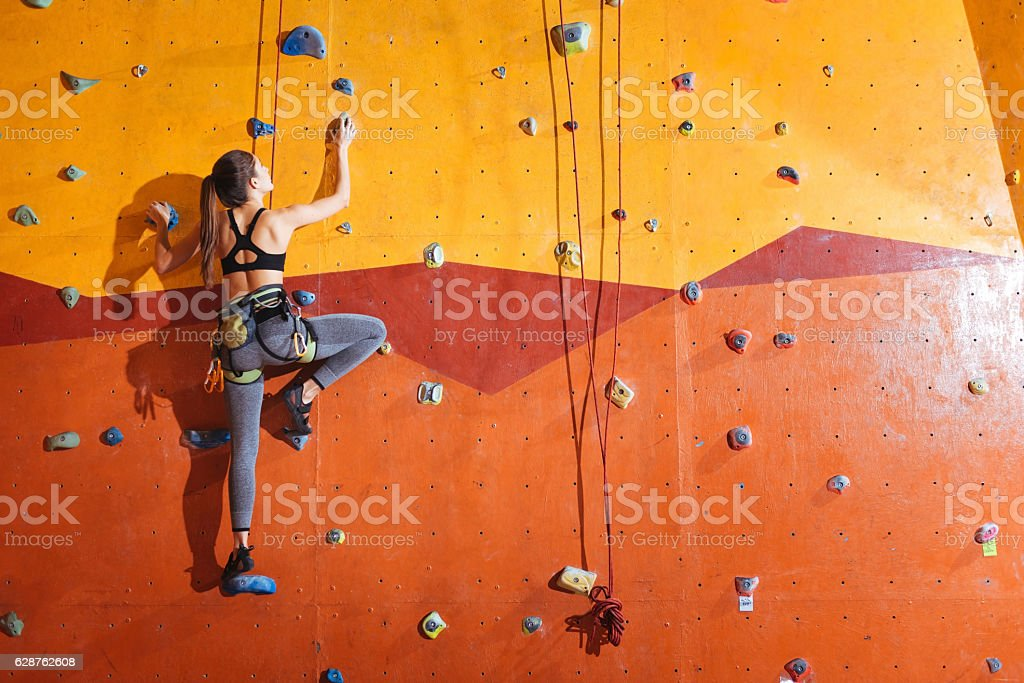Attractive woman climbing up the wall in gym stock photo