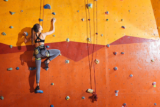 attractive woman climbing up the wall in gym - bergsteiger übung stock-fotos und bilder