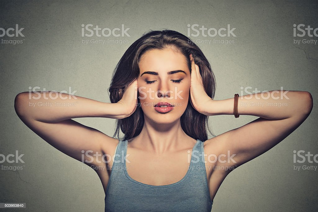 attractive woman covering with hands her ears stock photo