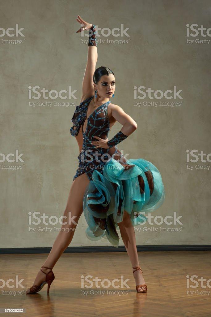 Attractive woman dancing ballroom dance in studio in gorgeous sexy latin costume stock photo