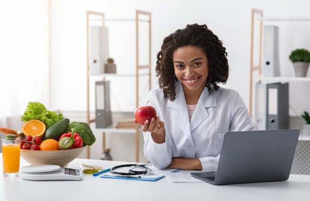 Attractive woman doctor kindly recommending eating fresh fruits stock photo