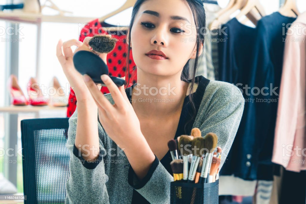 Attractive woman doing makeup with powder at home. Beauty and...