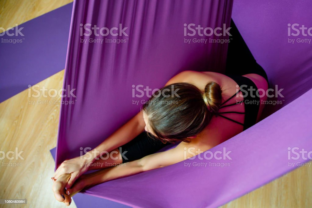 Attractive woman doing stretching exercises. Flying in the hammock. Attractive woman doing stretching exercises. Flying in the hammock. Activity Stock Photo