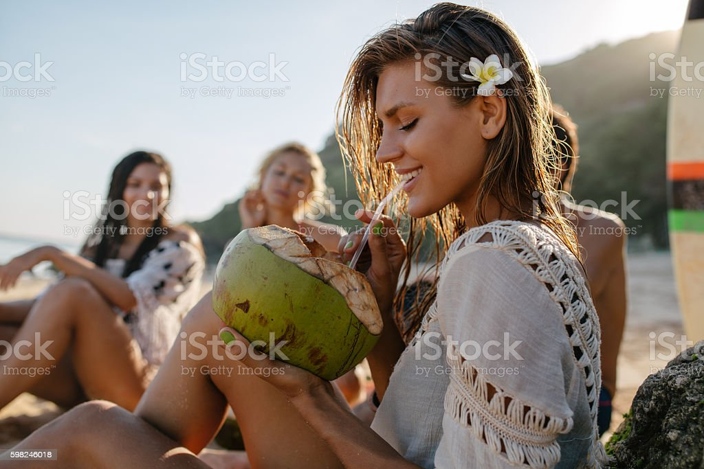 Attractive woman drinking coconut water with friends stock photo