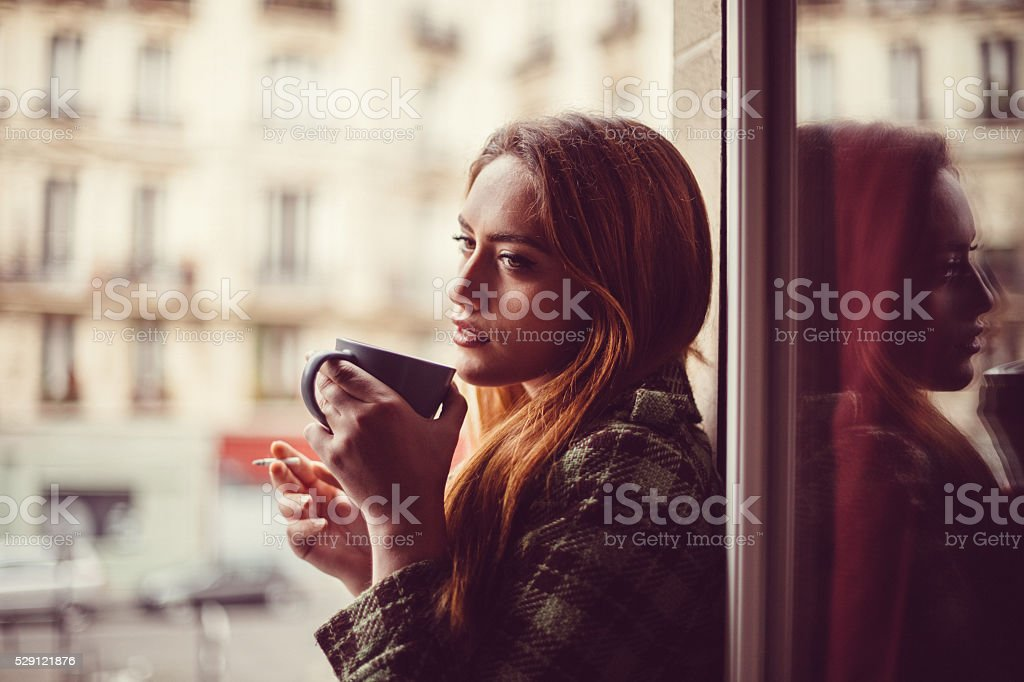 Attractive woman drinking coffee on the window stock photo