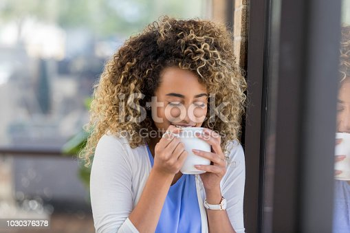 Happy young woman starts the day off with a fresh cup of coffee. She is smelling the coffee's aroma.