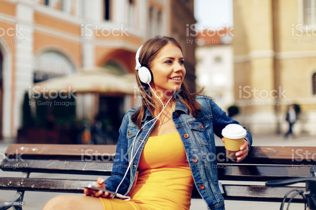 Attractive woman enjoying the music and coffee on a bench in downtown royalty free stockfoto