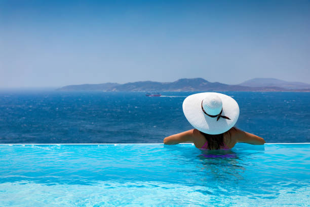 Attractive woman  enjoys the view from the pool to the Mediterranean sea stock photo