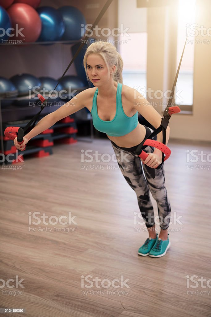 Attractive woman exercising on TRX stock photo