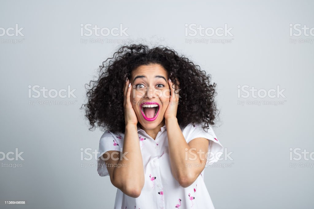 Attractive woman feeling excited Portrait of young attractive woman feeling excited on gray background. Female with hands on face shouting in joy. 20-24 Years Stock Photo