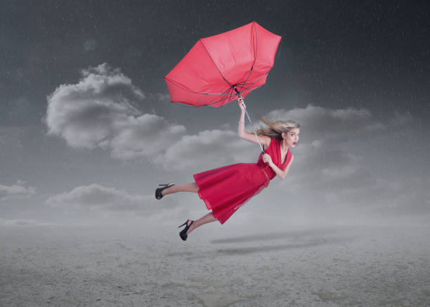 Royalty Free Woman Flying Away With Umbrella In A Storm ...