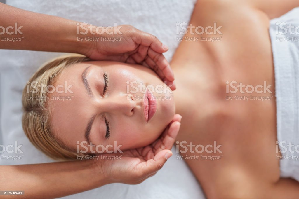 Attractive woman getting head massage at dayspa stock photo