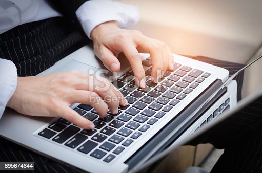 attractive woman hands typing on keyboard computer laptop working at outdoor.