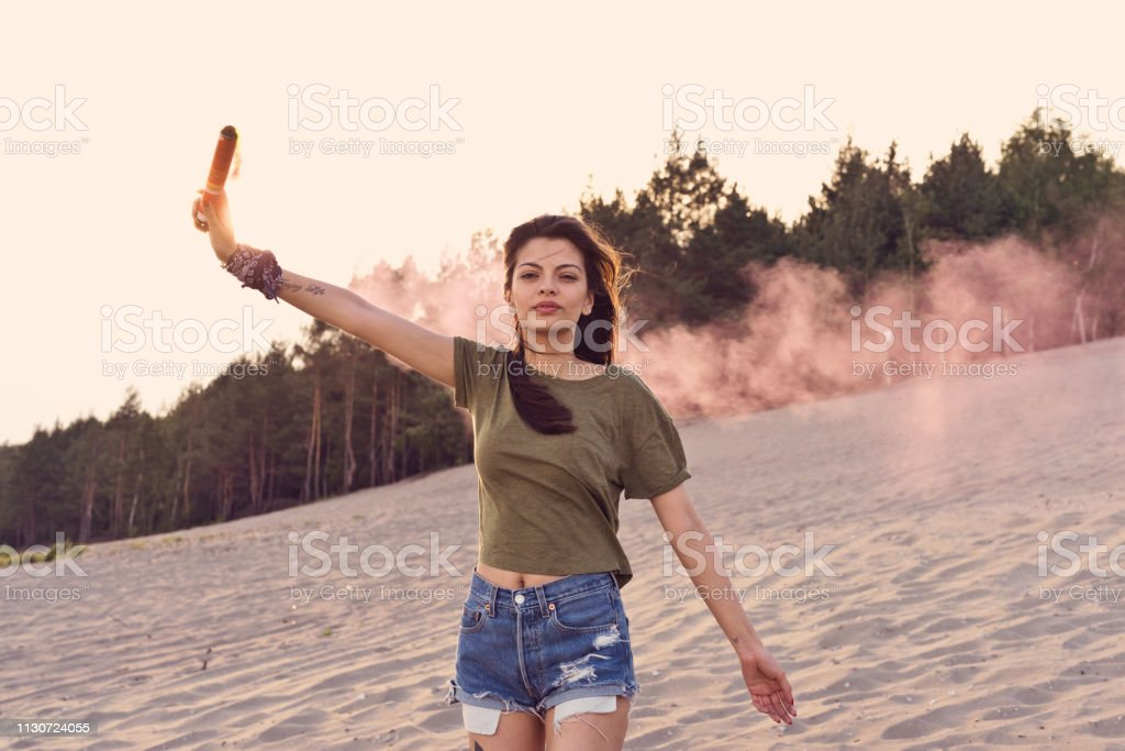 Attractive woman holding distress flare at desert Attractive woman holding distress flare at desert. Portrait of confident female is in casuals. She is walking on sand during summer vacation. 25-29 Years Stock Photo