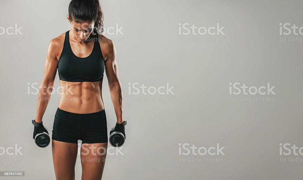 Attractive woman holding dumbbells facing downward stock photo
