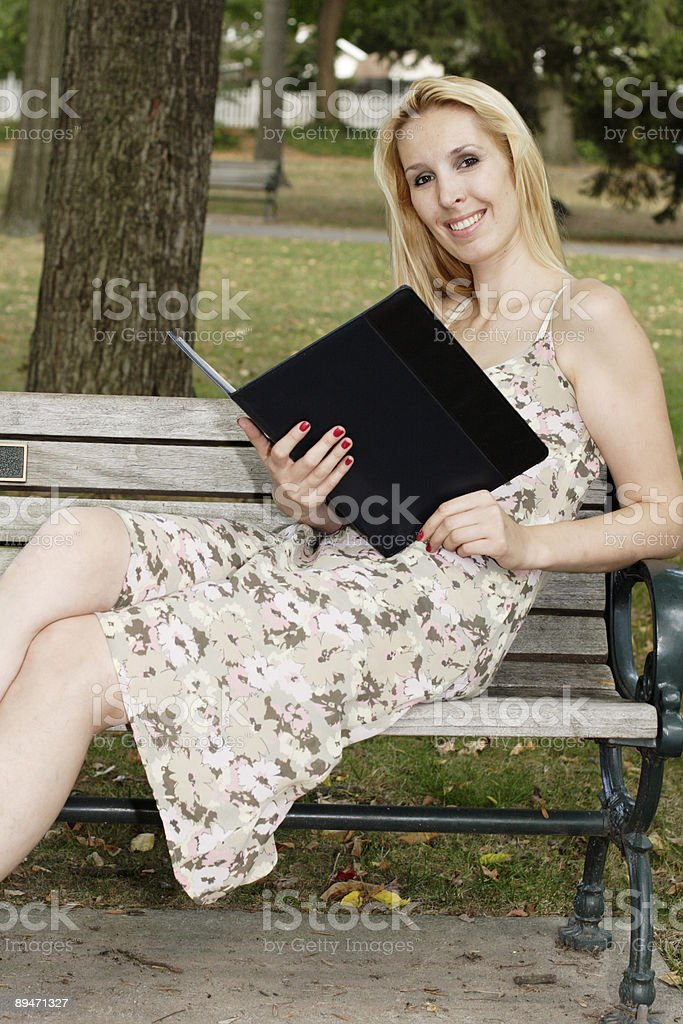 Attractive Woman Holding Folio and Simling at Camera royalty-free stock photo