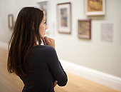Beautiful woman thoughtfully looking at pictures in a private gallery. Nikon D3X. Converted from RAW.