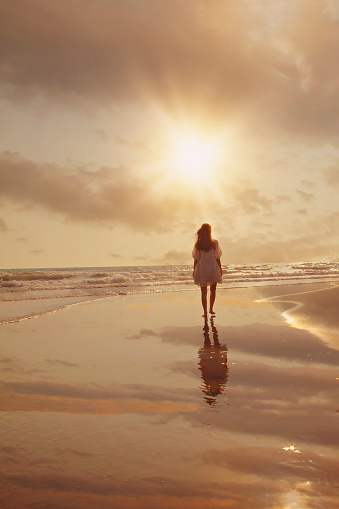 istock Attractive woman in beautiful dress on beach at sunset 1125722542