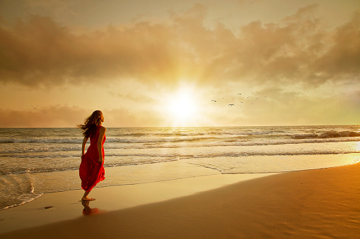 istock Attractive woman in beautiful dress on beach at sunset 1125969261