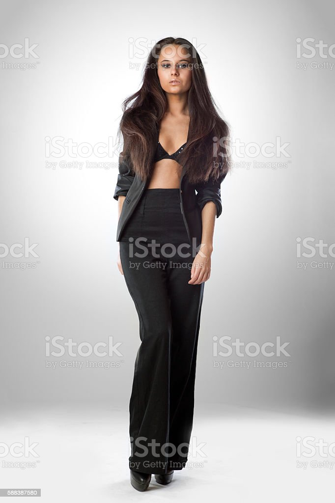 attractive woman in black dress walking on white stock photo