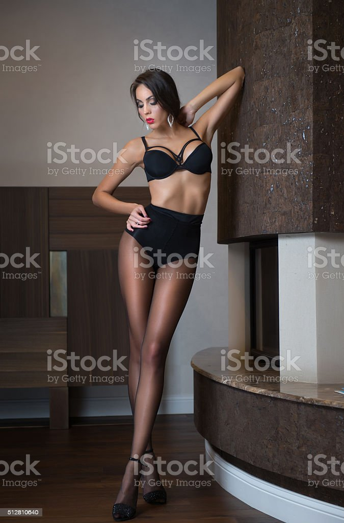 Attractive woman in black lingerie posing challenging stock photo