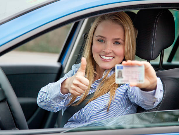 Attractive woman in car showing her drivers license stock photo