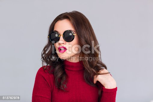 istock Attractive woman in glasses standing on grey background 513762978