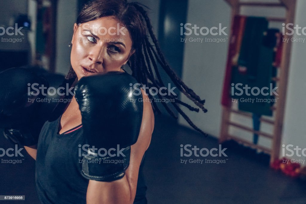 Attractive woman in gym with boxing gloves on stock photo