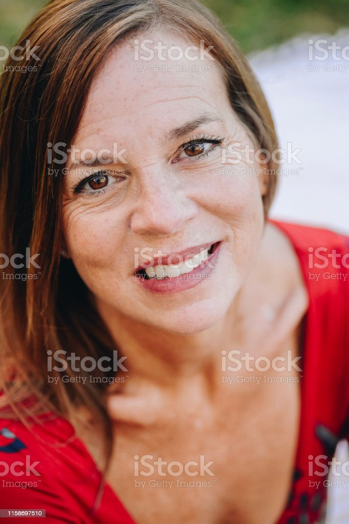 Attractive fit brunette woman in her 50's relaxes on a picnic blanket...