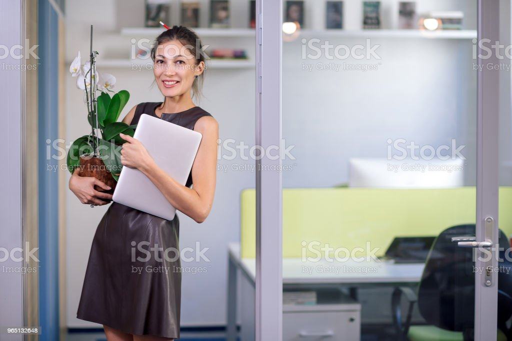 Attractive woman in leather dress holding laptop and orchid in a royalty-free stock photo