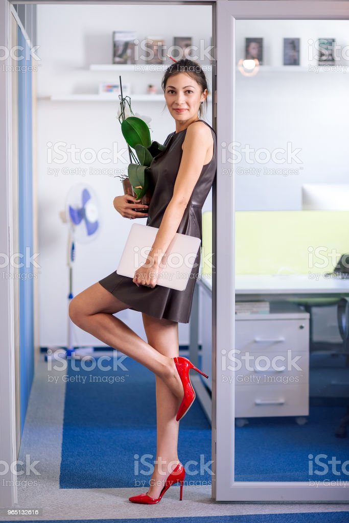 Attractive woman in leather dress moving in new office zbiór zdjęć royalty-free
