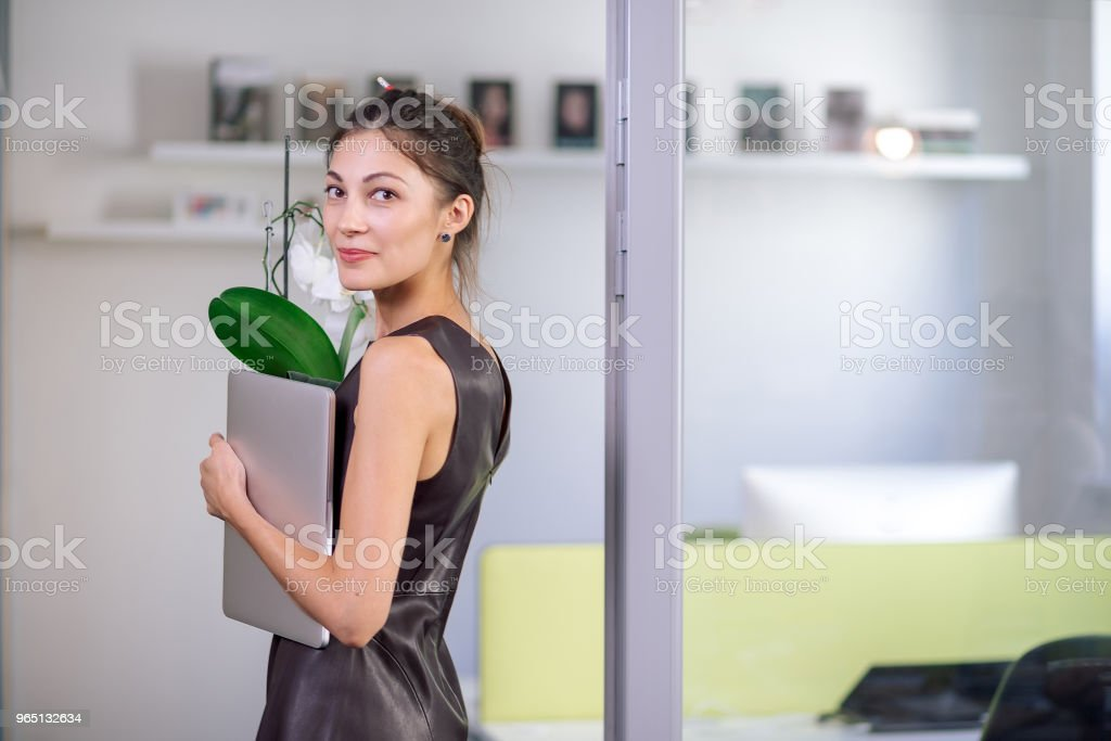 Attractive woman in leather dress smiling holding laptop zbiór zdjęć royalty-free