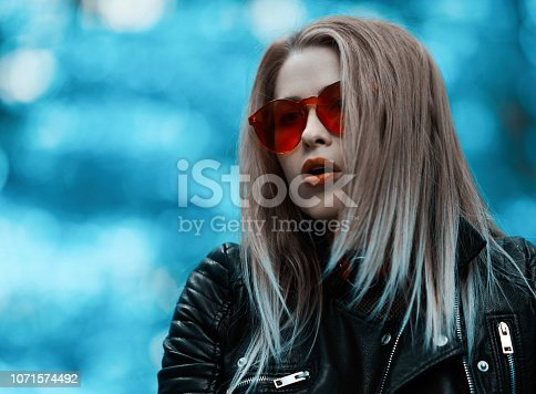 cool blond hair woman in the woodland posing with leather jacket and red sunglasses.